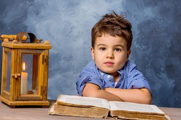 Kleiner Junge mit  Buch und Windlicht
