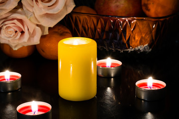 Still life of candles of different colors, flowers and fruits