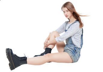 Young fashion girl in jeans overalls sitting isolated