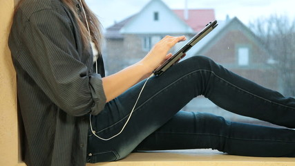 Girl listening to music with tablet computer sitting by window