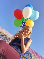 Mädchen mit Smartphone und Luftballons