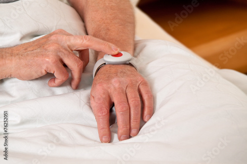canvas print picture Senior mit Rufhilfe Notfall Telefon im Bett