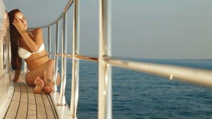 Young bikini woman enjoying summer vacation on deck of yacht
