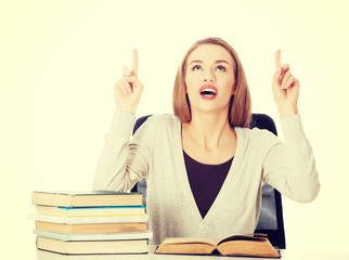 Woman sitting by stack of books and pointing up.