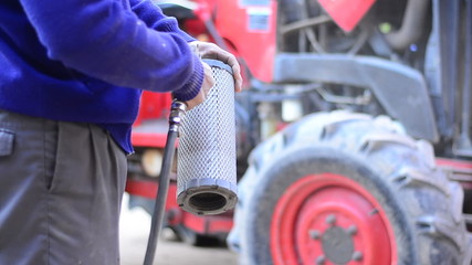 Farmer is cleaning pushcart engine air filter by air pump