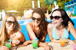 Women with beverages on summer party near the pool