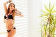 Sexy young blond woman posing in a black bikini