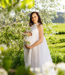 Pregnant woman in white dress in the flowering spring park