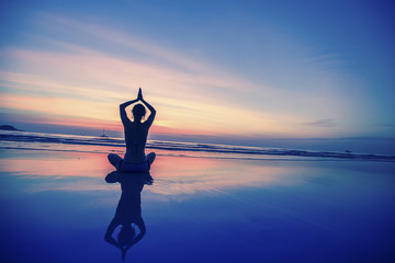 Lady practicing yoga on the ocean side.