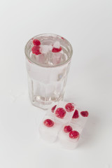 glass of water ice raspberries on a white background