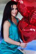 Beautiful brunette young woman with a heart-shaped balloons.