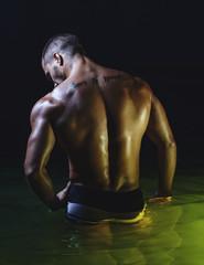 Muscled male torso in water