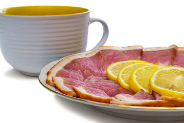 The dish with slices of ham and lemon on a white background.