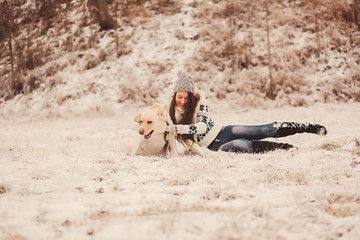 Funny portrait of young woman playing with labrador