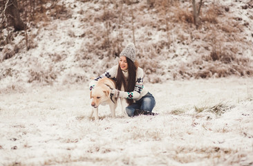 Portrait of cute young woman playing with dog in winter time