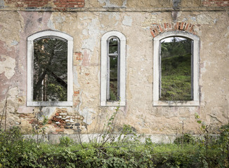 old broken windows on a rural house in ruins
