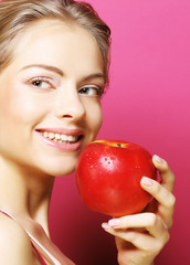woman with apple over pink background