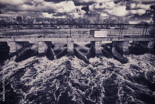 Fast Flowing Water Rushing Through a Bridge - 76261290