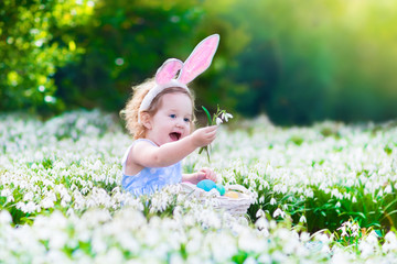 Happy  little girl on Easter egg hunt in flower's meadow
