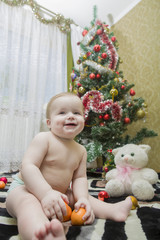 Happy child sits against the decorated fir-tree