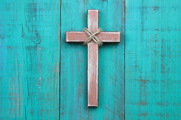 Wooden cross hanging on antique teal blue wall