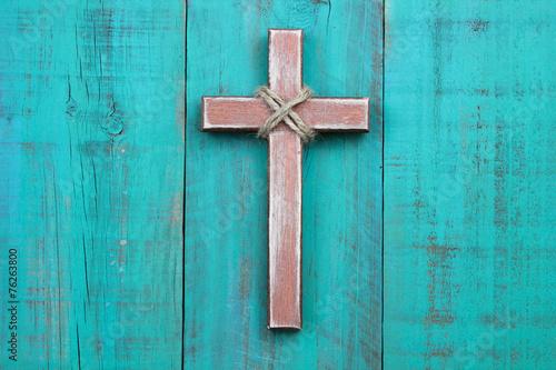 Drewniany krzyż wisi na antyczne turkusowy niebieski mur