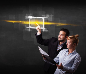 Young tech business couple touching button with orange light bea