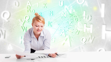 Business woman at desk with green word cloud