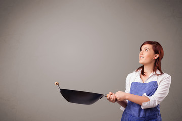 Young lady holding a frying pan