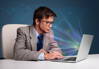 Handsome man sitting at desk and typing on laptop with abstract