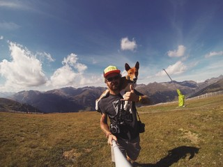 Man hikes in mountains with his dog on his shoulders