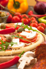 Pizza with ingredients, ready for baking
