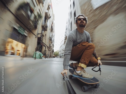 Man rides through city on skateboard Poster