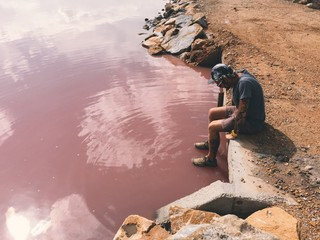 Man looks at pink water of Torrevieja lake and thinks