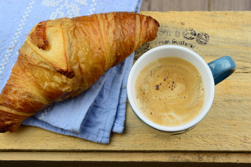Coffee with croissant on old wooden table