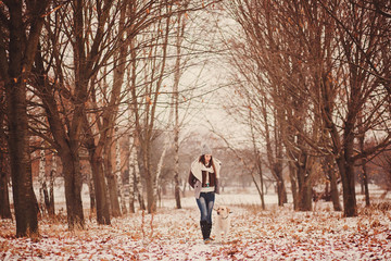 Happy girl and her dog walking in winter in a park