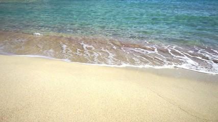 Strand mit klarem Wasser und Wellen