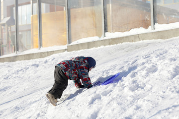 Child climbing on a snowy hill