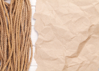 Brown rumpled cardboard paper background with marine rope