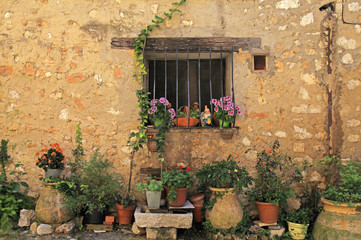 window in stone rural house with flower pots, Provence