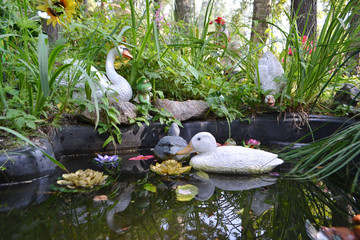 Artificial pond with toy ducks.