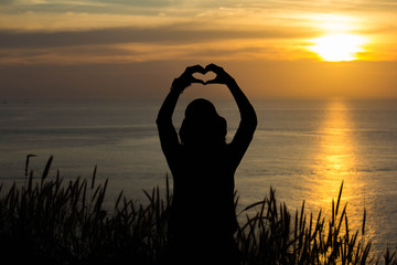 Silhouetted woman with a heart symbol at golden hour sunset