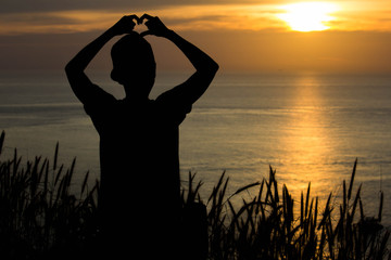 Silhouetted man with a heart symbol at golden hour sunset