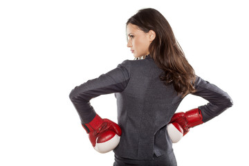Back view of business woman with boxing gloves on a white