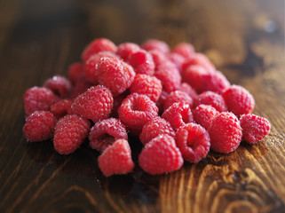 pile of raspberries on wooden table,