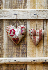 Two  hearts hanging over rustic wooden background.