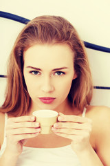 Woman in white lingerie is drinking small coffee