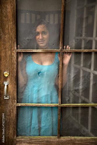 Fototapeta Young Indian Woman Gazing out Old Screen Door