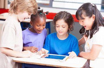 Multi-ethnic classroom playing with tablet. Happy school concept