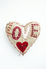 Fabric heart with letters LOVE over white background